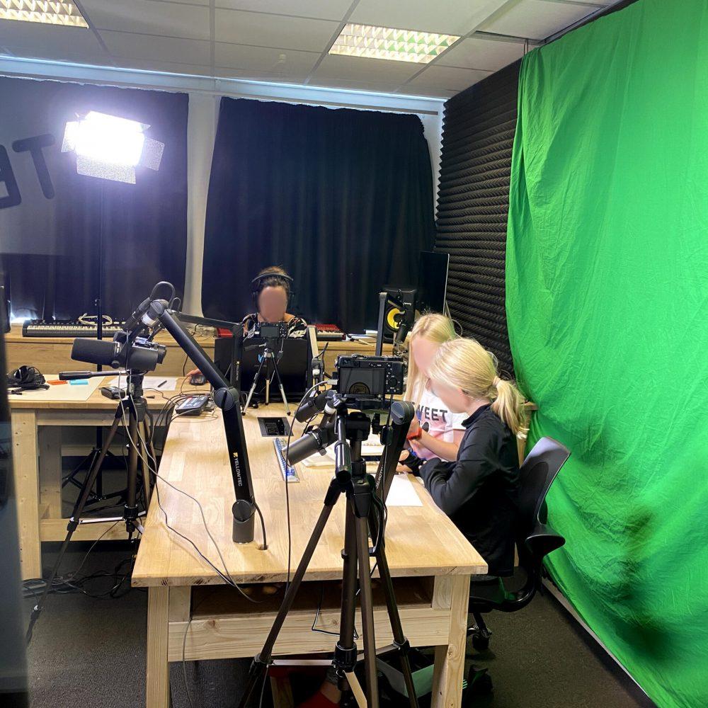Elever og lærer, der arbejder med greenscreen i et lydstudie